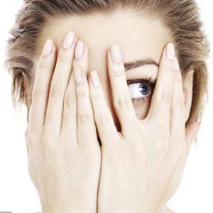 Femme mains devant de les jambes en laissant entrevoir juste un oeil