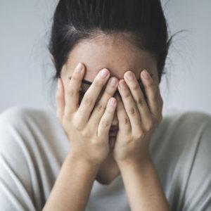 Femme apeurée les mains sur les yeux