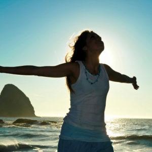 Femme souriant bras écartés au bord de l'eau
