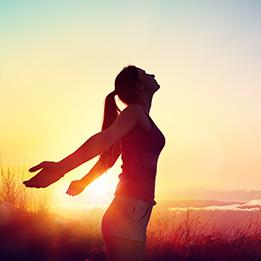 Femme tête vers le ciel et main dans le dos au crépuscule